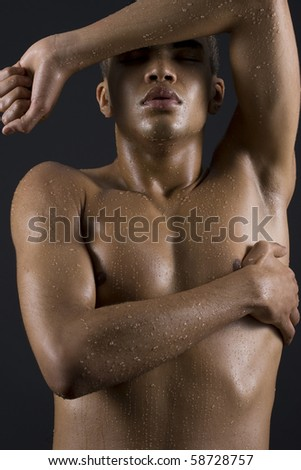 Drops of the water on the body of a young man on black background. - stock photo