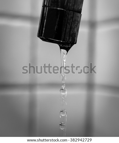 Drops of water falling from the tap and form a trail - stock photo