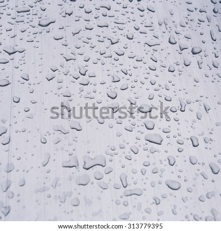 drops of water on a brushed steel surface - stock photo