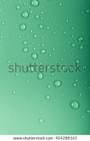 Drops of water on a color background. Green. Toned.