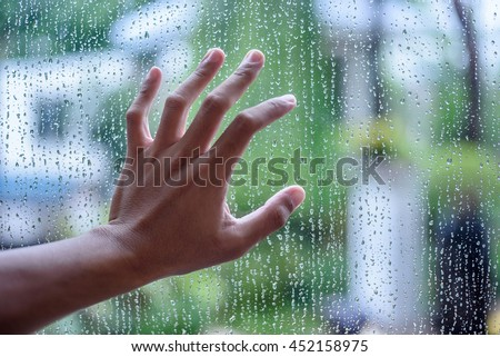 Drops of water on a glass and hand;