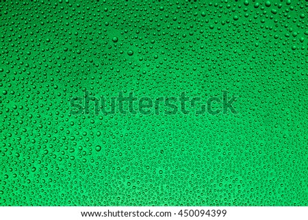 Drops of water on glass on a green background, shallow - stock photo