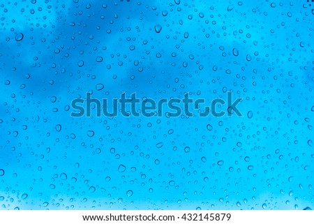 Drops of water on glass window over blue sky - stock photo