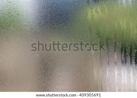 Drops of water on glass with green background