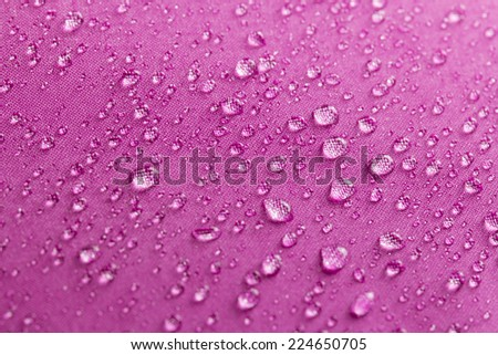 Drops of water on magenta umbrella - stock photo