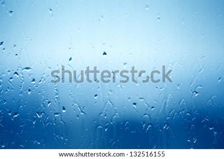 Drops of water on window glass, rainy weather - stock photo