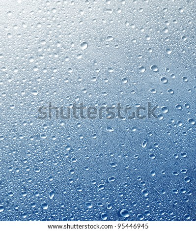 Drops on a glass surface with a blue color gradient background - stock photo