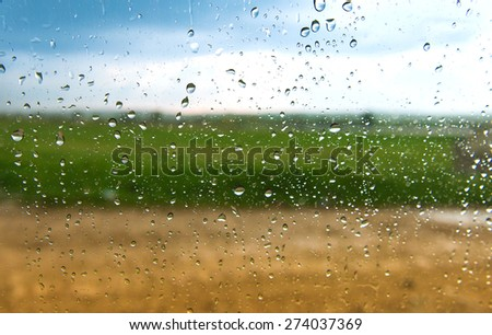 drops on the car window green grass and blue sky - stock photo