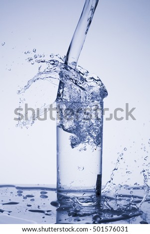 Drops, splashes, sprays, jets of water, a glass of water on a plastic background, studio lighting