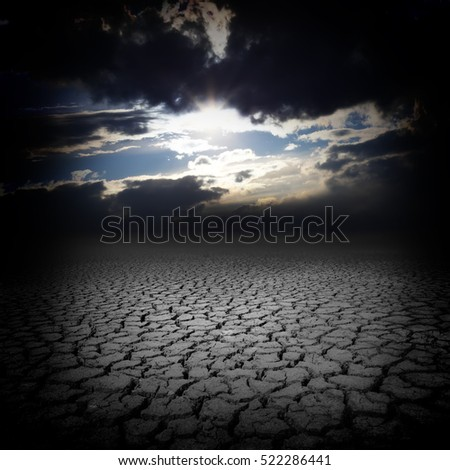 Drought cracks and dark sky clouds