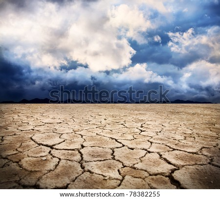 drought earth and storm dramatic sky at background - stock photo