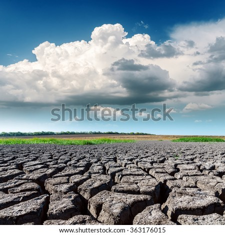 drought land closeup and low clouds in blue sky - stock photo