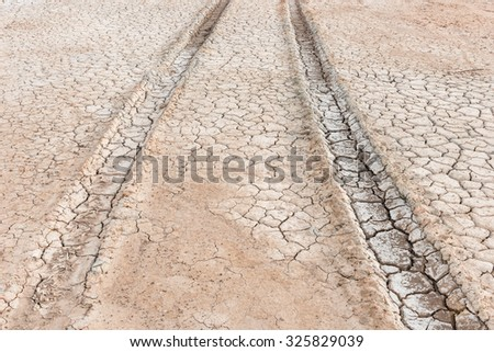 drought land, wheel tracks on the braked soil - stock photo