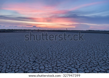 Drought land with earth crack pattern with colorful sky at dawn with cool tone. - stock photo
