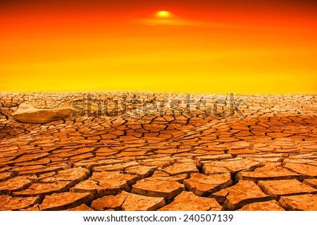 Drought land with yellow sunset - stock photo