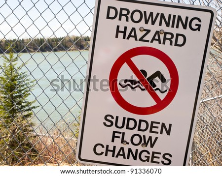 Drowning Hazard / No Swimming Sign beside dangerous river - stock photo
