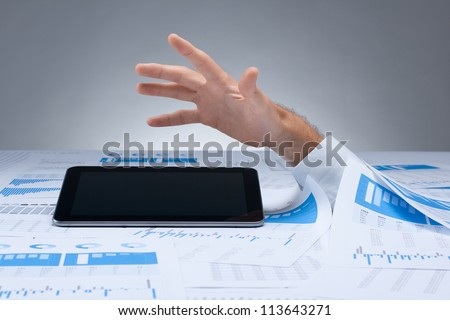 Drowning in paperwork and solution in digital tablet computer concept. White collar worker reaching out after tablet-pc computer - rescue of paperwork.