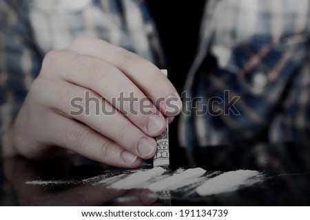 Drug abuse concept - man snorting cocaine - stock photo