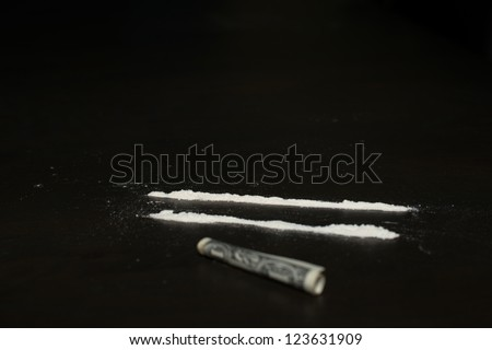Drug abuse: Two rows of cocaine being prepared for sniffing with a dollar bill lying in the front - stock photo