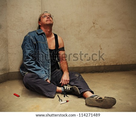 Drug Addict Injecting with a Syringe leaning against a filthy wall - stock photo