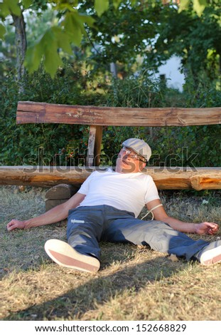 Drug addict lying in a park with his head resting on a wooden bench and a rope cuff around his arm and a disposable plastic syringe from shooting up the drugs at his side - stock photo