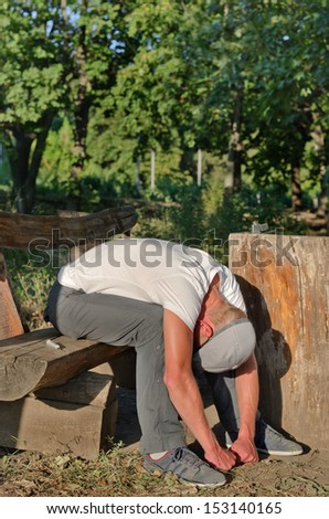 Drug addict on a downer after shooting up drugs and enjoying the euphoria sitting bending forwards on a park bench with his balled fists resting on the ground as he fights the depression - stock photo