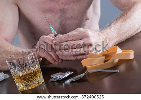 Drug addict preparing a dose of heroin - stock photo