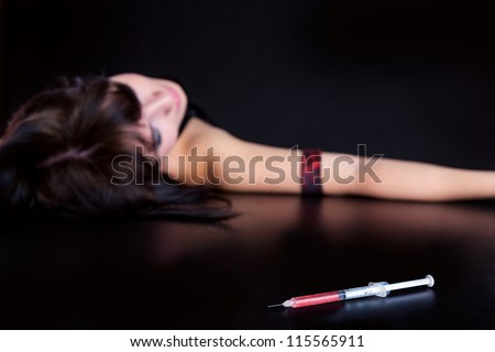 Drug addict woman with syringe is sleeping on table. Simulated, studio shot. Focus is on the syringe - stock photo