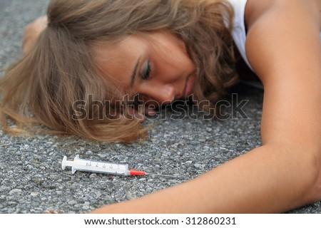 Drug-addicted Teenager with syringe lying on a street 2 - stock photo