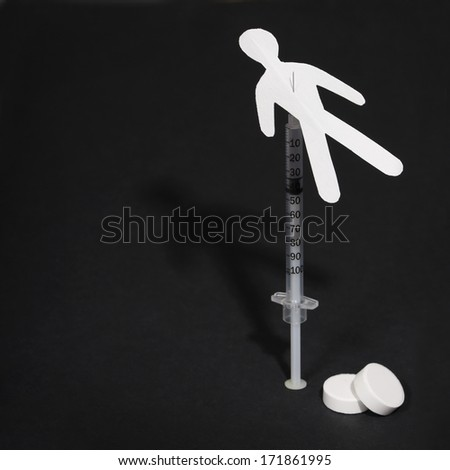 Drug Addiction Concept. Paper man with syringe and pills over black background - stock photo