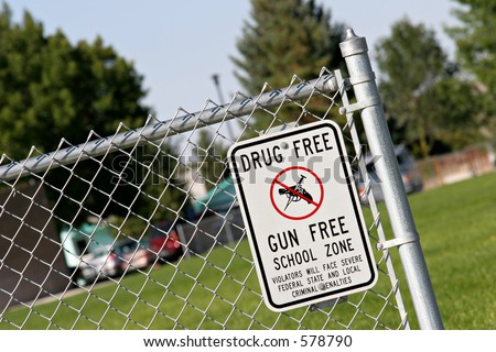 drug and gun free school zone sign at a school yard. sign of the times. - stock photo