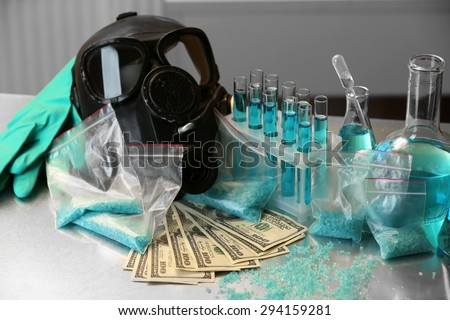 Drug laboratory: blue  methamphetamine and money on table close up - stock photo