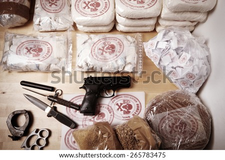 Drug packages, raw opium, drug dozens and weapons seized by police - stock photo