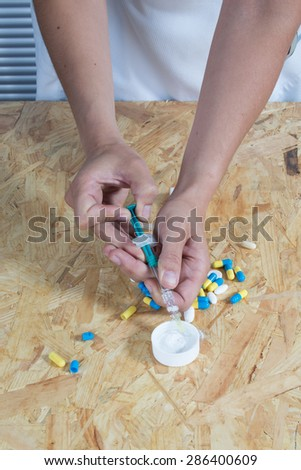 Drug syringe and cooked heroin on wooden table