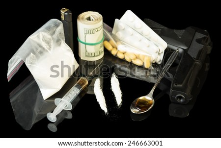 Drug syringe and heroin with pills over money - stock photo