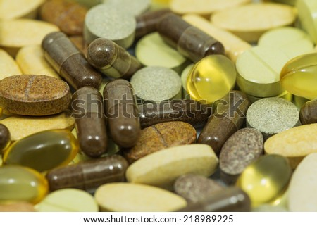 Drugs and food supplements pills and capsules macro background - stock photo