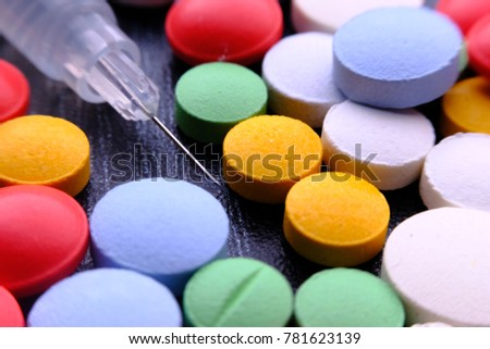 Drugs and syringes on wooden table with room for text