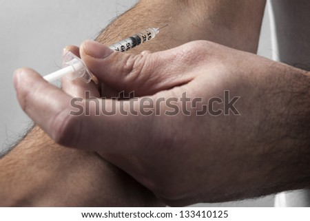 Drugs injected into male hand under studio lights - stock photo