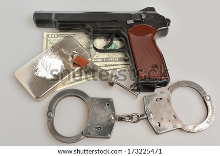 Drugs, syringe with blood, pistol, handcuffs and money on gray background - stock photo