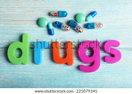 Drugs word formed with colorful letters on wooden background