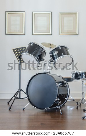Drum and bass set on wooden floor - stock photo