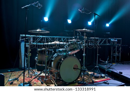 Drum Kit on stage backlit with stage lighting. - stock photo