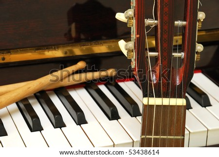 Drum sticks, guitar and piano keyboard. For concepts like music composition and creativity. - stock photo