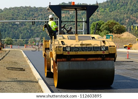 Drum tandem vibratory rollers compacting down a fresh layer of paving on a new road interchange project - stock photo