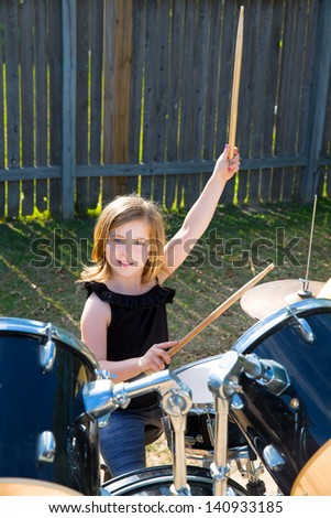 Drummer blond kid girl playing drums in the backyard lawn - stock photo