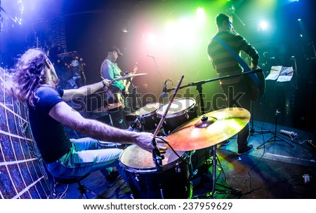 Drummer (blurred motion) playing on drum set on stage. Focus on the drum and microphone. Warning - authentic shooting with high iso in challenging lighting conditions. - stock photo