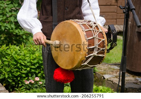 Drummer play folk music with drum and stick in rural village party.  - stock photo