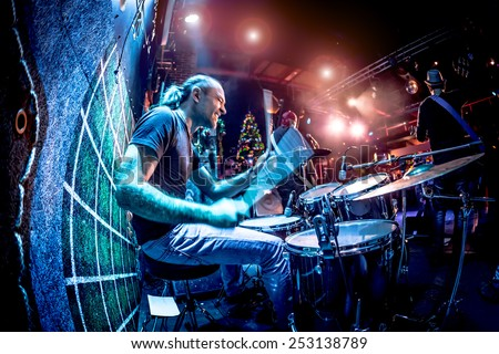 Drummer playing on drum set on stage. Warning - Focus on the drum, authentic shooting with high iso in challenging lighting conditions. A little bit grain and blurred motion effects. - stock photo