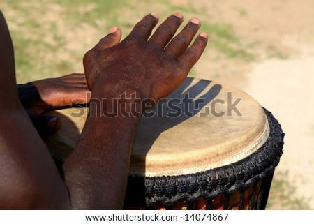 Drummer's hands playing a leather head drum - stock photo