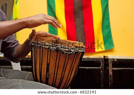 Drummer's hands playing in indoor party - shot against South African flag. Shot in Stellenbosch, Western Cape, South Africa. - stock photo